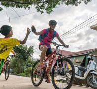 The local kids line up for high fives on our Cambodia biking tour