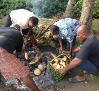 Our hosts digging up our lovu dinner cooked Fiji style